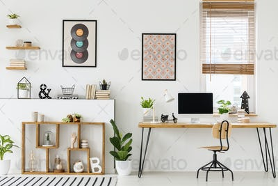 Real photo of a desk with a mockup computer screen, ornaments an