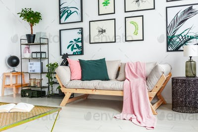 Real photo of a sofa standing next to a wall with paintings and