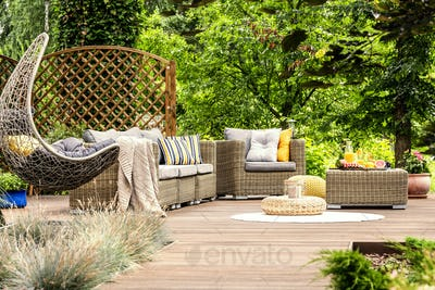Wooden veranda with rattan furniture, comfy swing and trees in t