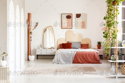 Mirror on cabinet next to orange bed under posters in bright bed