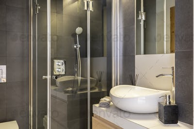 Bathroom interior with white, ceramic washbasin and shower cabin
