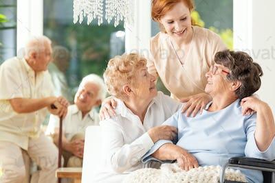 Happy friendship in old age. Tender caregiver standing behind se