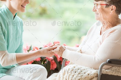 Nurse preparing a disabled pensioner for a walk in the garden of