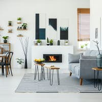 Black chairs at dining table in bright living room interior with