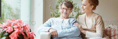 Professional caretaker with her senior charge sitting on a sofa