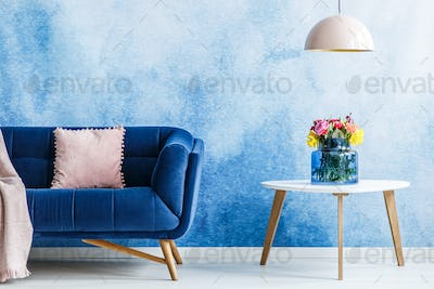 Comfortable plush settee with pastel cushion and a side table wi