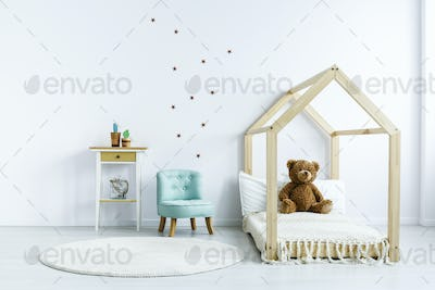 Teddy bear on wooden bed next to blue chair in white kid's bedro