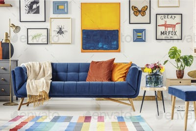 Painting above navy blue couch in artistic living room interior
