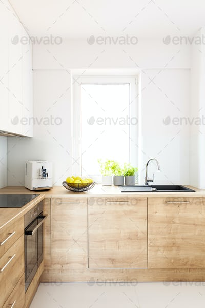 Wooden cabinets in bright minimal white kitchen interior with wi