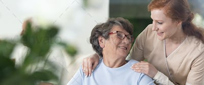 Close-up of a tender caregiver with her hands on the shoulders o