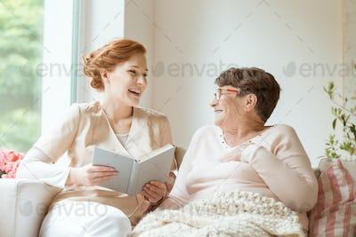 Happy nurse reading a funny book to her elderly patient in a pri