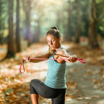 Woman Exercising With Elastic Band Outdoors in The Fall