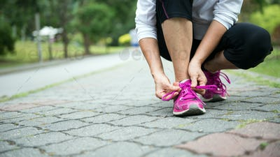 Jogger tighten her running shoe laces