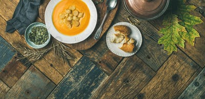 Fall pumpkin cream soup with croutons and seeds, wide composition
