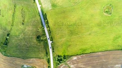 Aerial view of a country road with a cars between agricultural fields