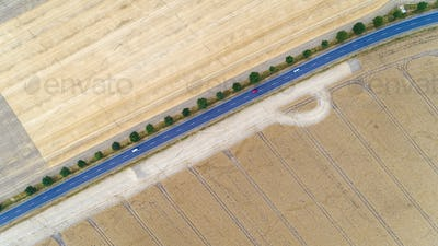Aerial view of a country road with cars between agricultural fields in Europe