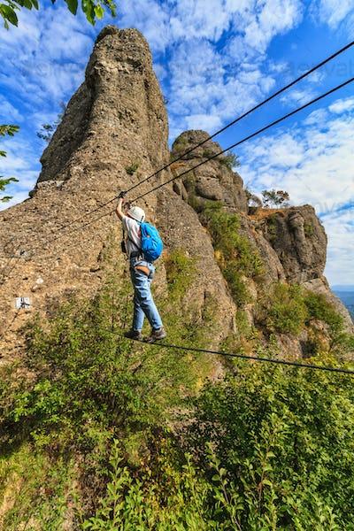 Climber on via ferrata bridge