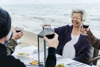 Mature friends drinking wine at the beach