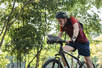 Senior cyclist checking a map