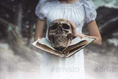 Female victim holds book and human skull in hand