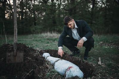 Maniac against grave, serial murderer concept