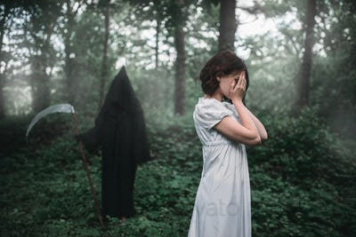 Young female victim in white dress in the forest