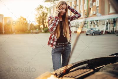 Car breakdown, sad woman against open bonnet
