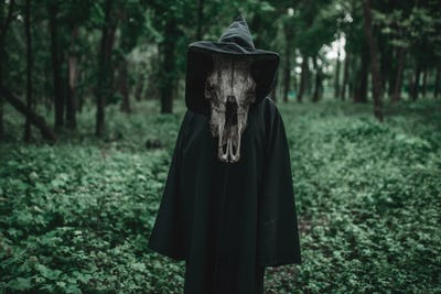 Death in a black hoodie with a scythe in forest