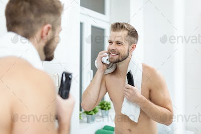 Handsome bearded man trimming his beard with a trimmer