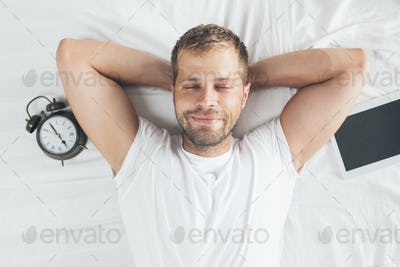 Man sleeping on bed after using his digital tablet