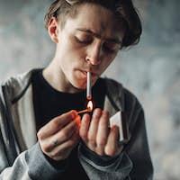 Male drug addict light a cigarette