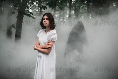 Female victim in white dress in the misty forest