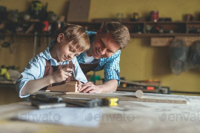 Smiling father and son at work