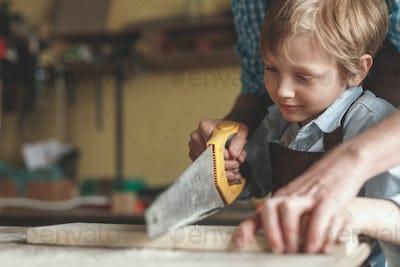 Little boy sawing a plank