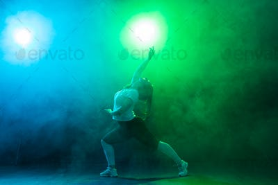 Young woman demonstrates flexibility over colored background.