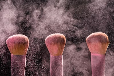 Three brushes for makeup with pink make-up mineral powder in motion on a black background