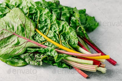 Fresh raw swiss rainbow chard leaves on gray background.