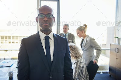Black businessman standing in front of team