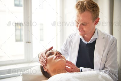 Young beautician holding female head before treatment procedure