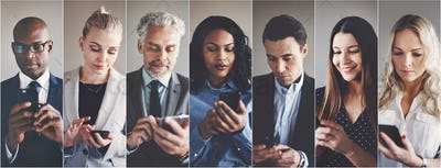Diverse group of businesspeople reading text messages on cellphones