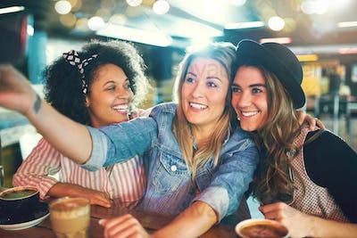 Three fun young women posing for a selfie