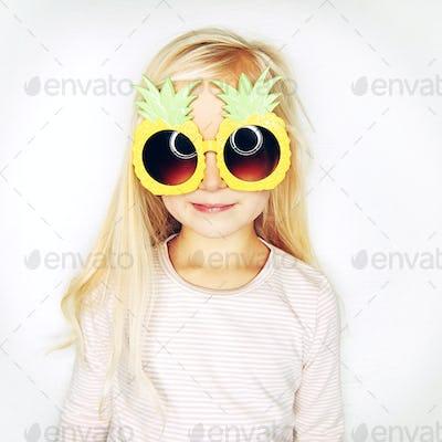 Little girl in pineapple sunglasses in studio