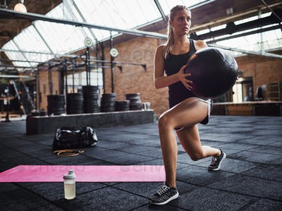 Fit woman exercising with a swiss ball at the gym