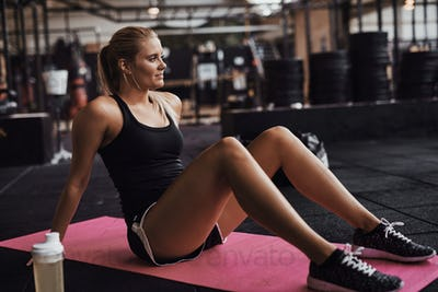 Smiling young woman sitting on the floor of a gym