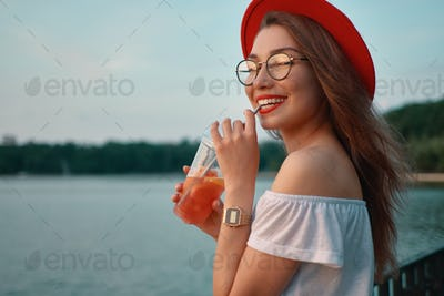 A Young stylish woman having a refreshing drink while walking