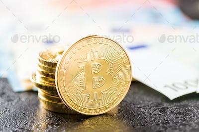Golden bitcoins and euro banknotes.