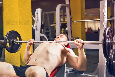 Man doing heavy exercise pumping up muscles on bench press