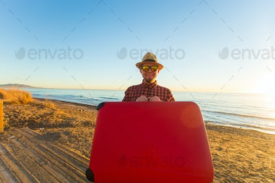 Man in glasses and hat carring his red suitcase near the sea