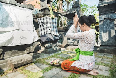 balinese woman praying at temple on small shrines in houses
