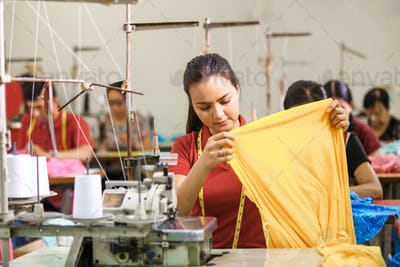 Seamstress in textile factory sewing using industrial sewing mac